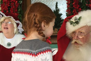 Girl With Mr. and Mrs. Santa Claus